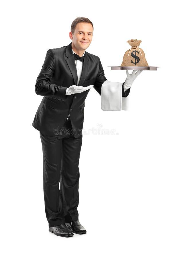 Οικονόμος που κρατά έναν δίσκο με μια τσάντα χρημάτων σε το στοκ εικόνες