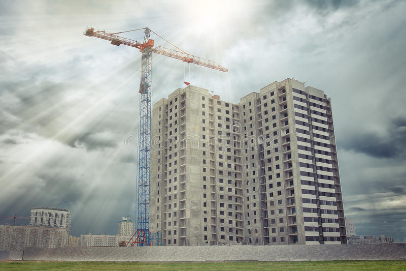 Οικοδόμηση ενός νέου κατοικημένου κτηρίου πολυ-διαμερισμάτων με το γερανό στοκ φωτογραφία