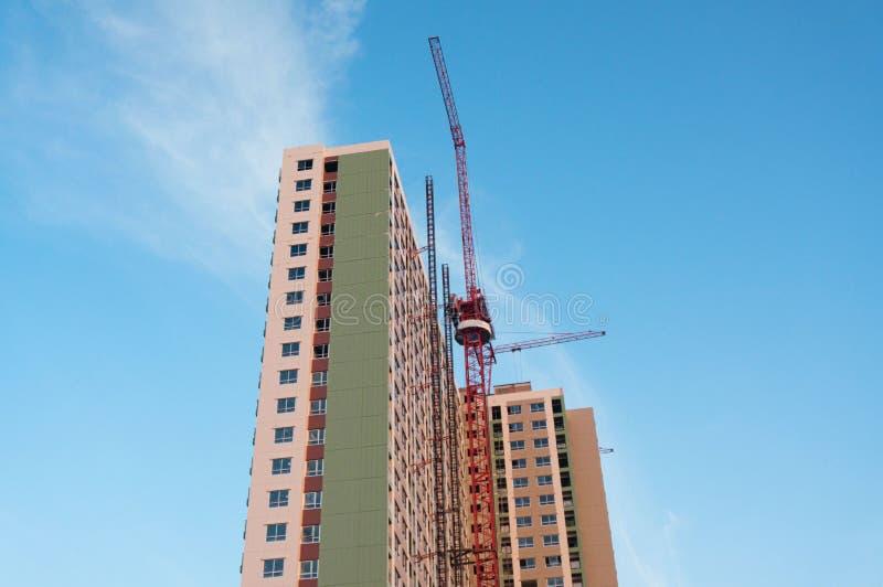 Οικοδόμηση κτηρίου με τον κόκκινο γερανό στο υπόβαθρο μπλε ουρανού στοκ εικόνες