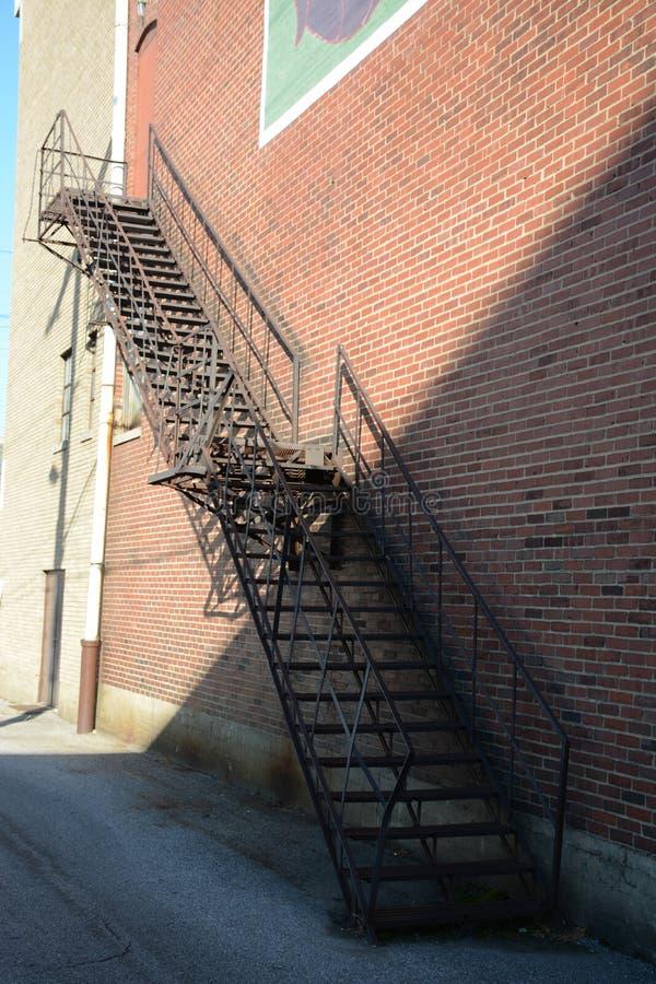 οικοδόμηση τούβλου κάτω από διαφυγών σύγχρονα σκαλοπάτια μετάλλων πυρκαγιάς τα κύρια στοκ εικόνα