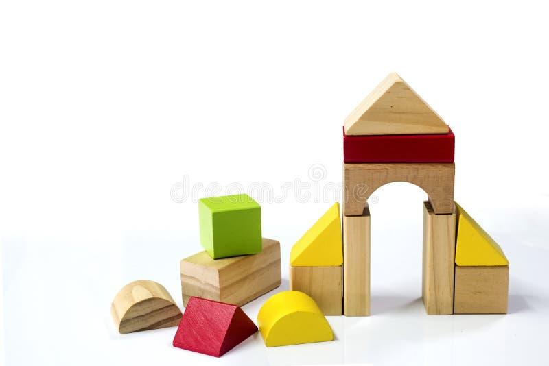 Οικοδόμηση των ξύλινων τούβλων children& x27 οι ξύλινοι κύβοι παιχνιδιών του s απομονώνουν σε ένα W στοκ εικόνες
