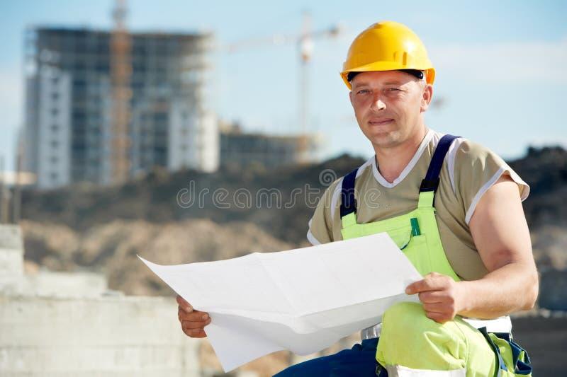 Οικοδόμος μηχανικών στο εργοτάξιο οικοδομής με το σχέδιο στοκ εικόνες