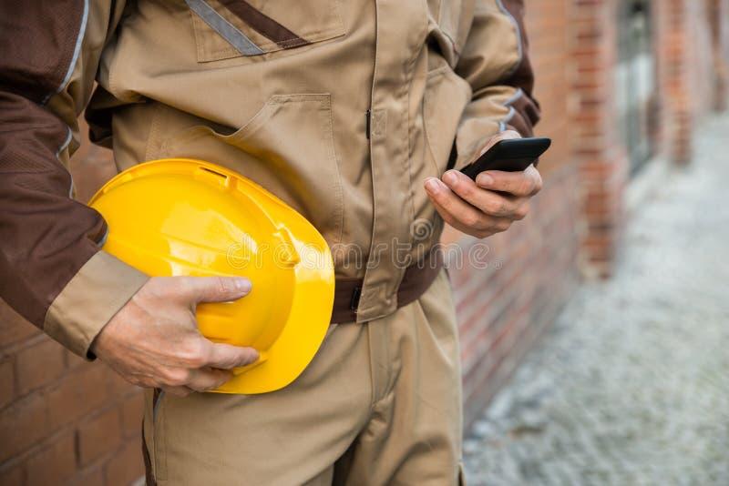 Οικοδόμος που χρησιμοποιεί το κινητό τηλέφωνο στοκ φωτογραφία με δικαίωμα ελεύθερης χρήσης