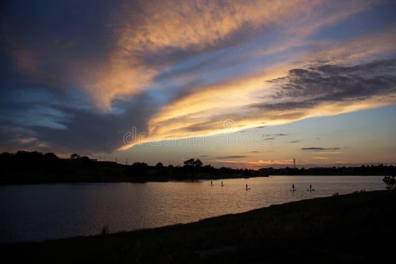 Οικότροφοι κουπιών στη λίμνη στο ηλιοβασίλεμα στο δυτικό Τέξας στοκ εικόνες