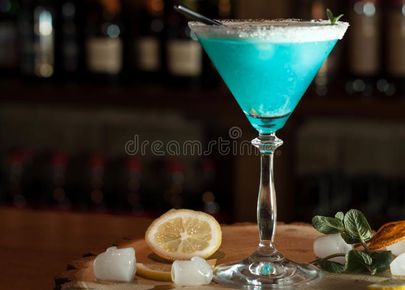 Οινοπνευματώδες ποτό στο γυαλί με το μαύρο άχυρο κατανάλωσης, τις φέτες λεμονιών και τα χορτάρια στοκ εικόνες