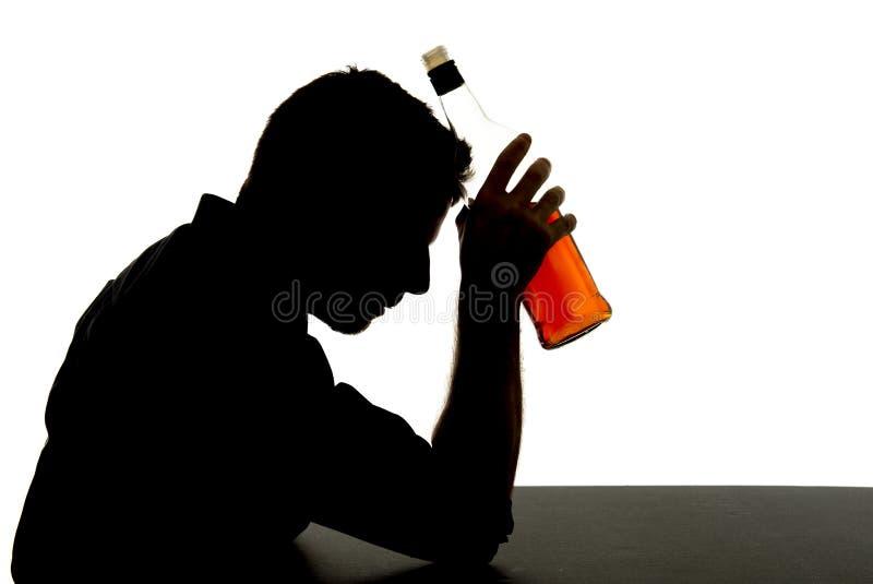 Οινοπνευματώδες πιωμένο μπουκάλι ουίσκυ εκμετάλλευσης ατόμων στη σκιαγραφία προβλήματος εθισμού στοκ εικόνες με δικαίωμα ελεύθερης χρήσης