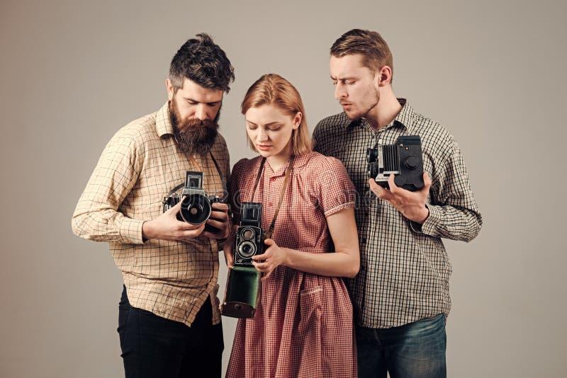 Οι άνδρες, γυναίκα στα ενδιαφερόμενα πρόσωπα εξετάζουν τη κάμερα στο γκρίζο υπόβαθρο Επιχείρηση των πολυάσχολων φωτογράφων με τις στοκ εικόνες