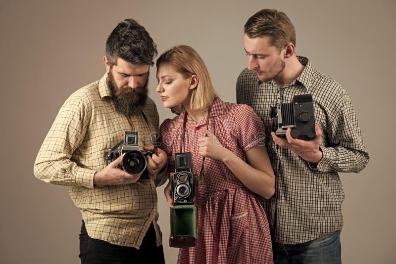 Οι άνδρες, γυναίκα στα συγκεντρωμένα πρόσωπα εξετάζουν τη κάμερα, γκρίζο υπόβαθρο Επιχείρηση των πολυάσχολων φωτογράφων με τις πα στοκ εικόνα