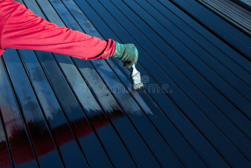 Οι άνδρες εργαζόμενοι που φορούν τις κόκκινες τηβέννους είναι χρωματισμένοι στοκ φωτογραφία με δικαίωμα ελεύθερης χρήσης