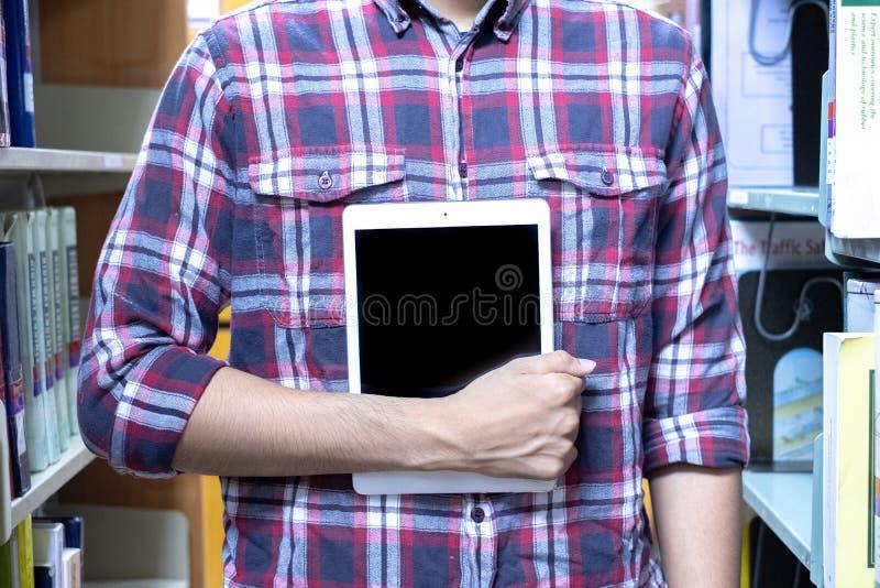 Οι άνδρες σπουδαστές χρησιμοποιούν την τεχνολογία για να βρούν τα βιβλία για να διαβάσουν στη βιβλιοθήκη r στοκ εικόνες με δικαίωμα ελεύθερης χρήσης
