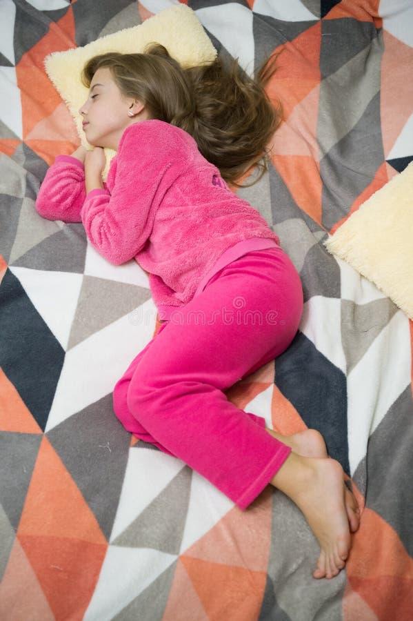 Οι άνετες πυτζάμες για χαλαρώνουν Το παιδάκι κοριτσιών φορά τις μαλακές χαριτωμένες πυτζάμες χαλαρώνοντας στο κρεβάτι Κουρασμένη  στοκ εικόνες