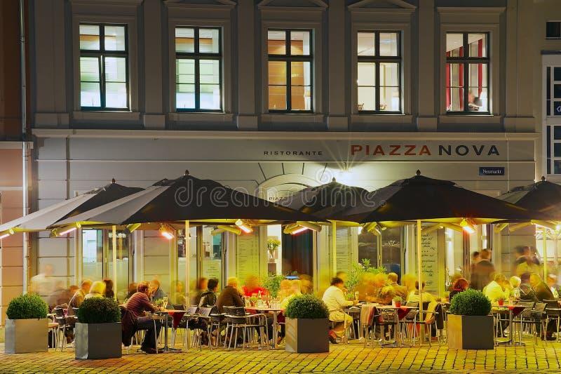 Οι άνθρωποι έχουν το όψιμο γεύμα έξω από ένα εστιατόριο στο κεντρικό τετράγωνο στη Δρέσδη, Γερμανία στοκ εικόνα