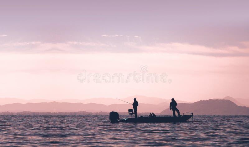 Οι άνθρωποι αλιεύουν στη βαθιά βάρκα στη λίμνη στοκ φωτογραφία