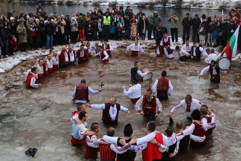"""Οι άνθρωποι εκτελούν τον εθνικό χορό """"Horo """"στα παγωμένα νερά του ποταμού Iskar στο χωριό Zverino στοκ φωτογραφίες με δικαίωμα ελεύθερης χρήσης"""