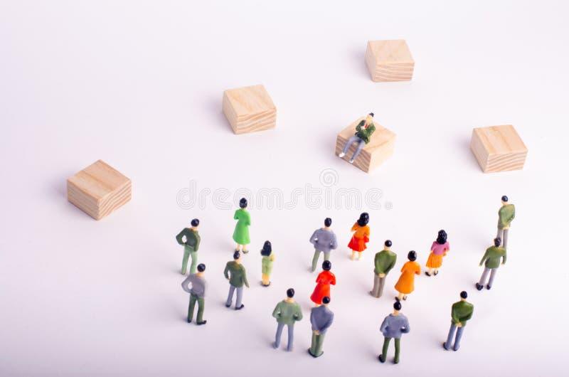 Οι άνθρωποι εξετάζουν τη συνεδρίαση προσώπων Οι άνθρωποι καταδικάζουν ένα πρόσωπο Το πλήθος θαυμάζει το είδωλό τους Όχι όπως σε,  στοκ εικόνες