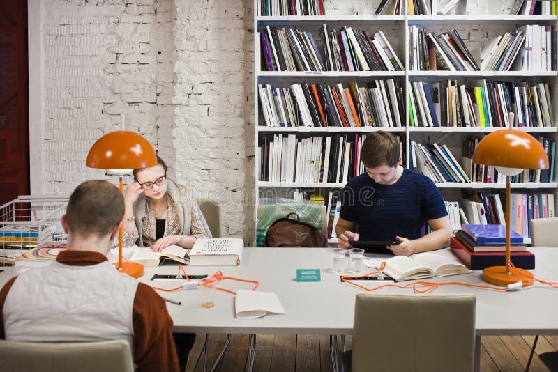 Οι άνθρωποι διαβάζουν τα βιβλία στη βιβλιοθήκη στοκ εικόνα με δικαίωμα ελεύθερης χρήσης