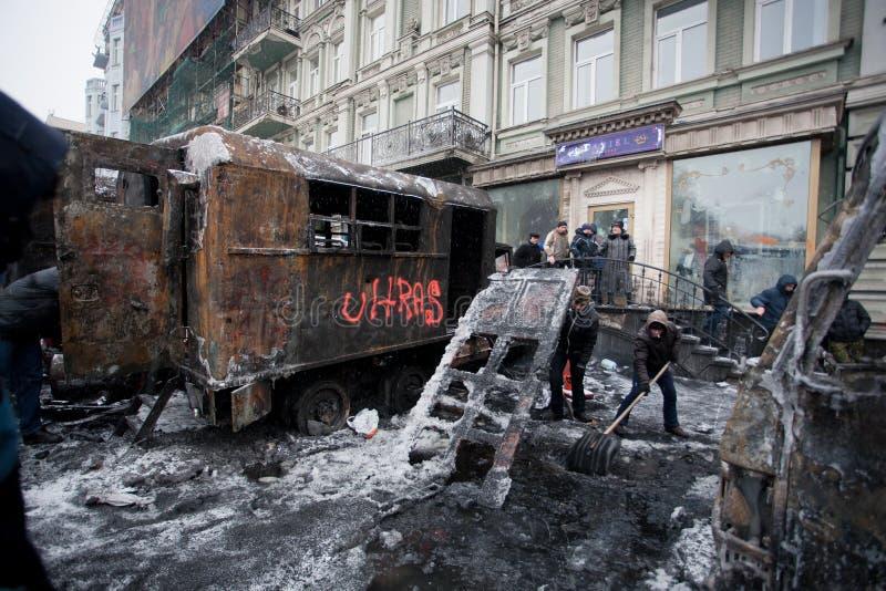 Οι άνθρωποι καθαρίζουν τη χειμερινή οδό με την πάγος-καλυμμένη μεταφορά που καίγεται στις πάλες με τις ομάδες αστυνομίας στοκ φωτογραφίες με δικαίωμα ελεύθερης χρήσης