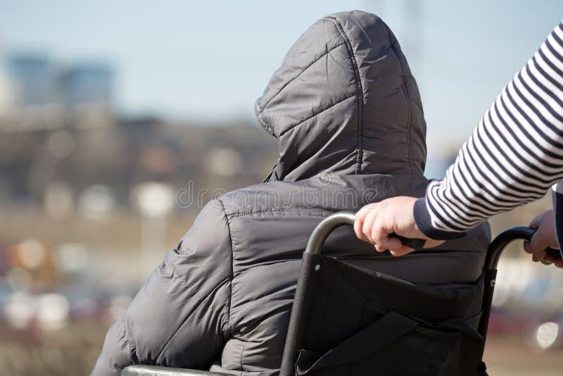 Οι άνθρωποι με την περιορισμένη κινητικότητα παίρνουν έναν περίπατο από την αναπηρική καρέκλα στοκ φωτογραφία