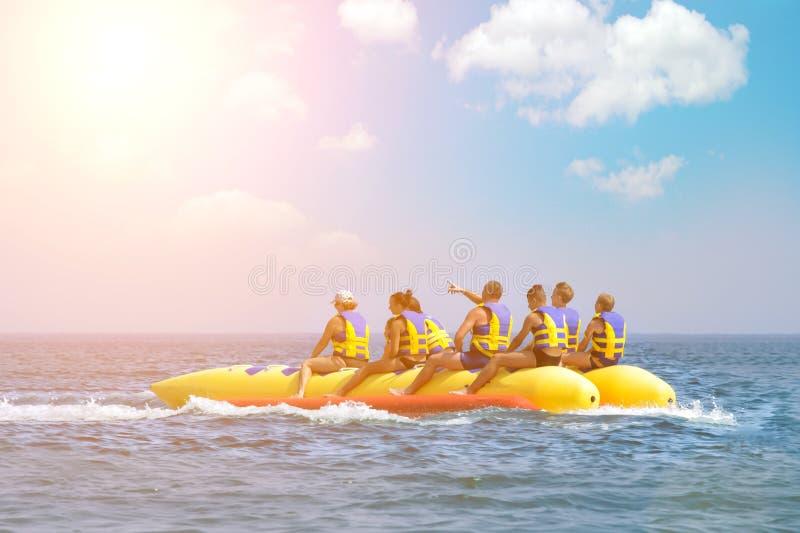 Οι άνθρωποι οδηγούν στη βάρκα μπανανών Φωτεινοί μπλε θάλασσα και μπλε ουρανός με τα σύννεφα ευτυχείς διακοπές Αθλητισμός νερού πα στοκ φωτογραφία