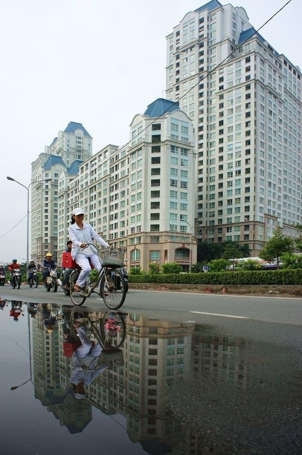 Οι άνθρωποι οδηγούν το ποδήλατο με το υπόβαθρο πολυκατοικίας στοκ εικόνα