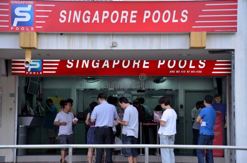 Οι άνθρωποι περιμένουν στη σειρά έξω από τη Σιγκαπούρη συγκεντρώνουν το κατάστημα στοιχημάτισης στοκ εικόνα