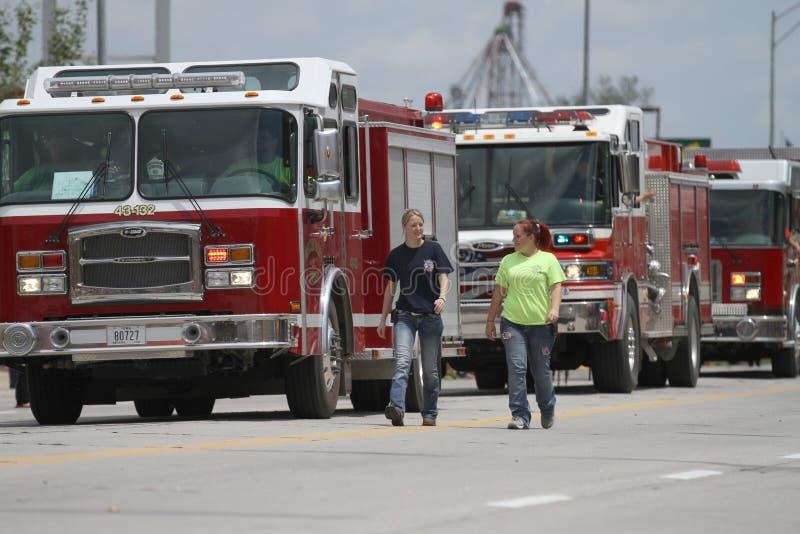 Οι άνθρωποι περπατούν με τα πυροσβεστικά οχήματα σε μια παρέλαση στη μικρού χωριού Αμερική στοκ φωτογραφίες με δικαίωμα ελεύθερης χρήσης