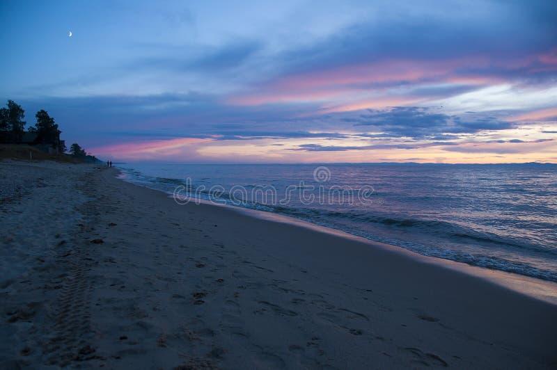 Οι άνθρωποι περπατούν στην παραλία της λίμνης Baikal στο ηλιοβασίλεμα στοκ εικόνα