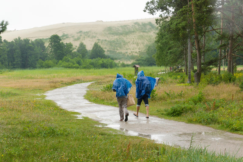 Οι άνθρωποι πηγαίνουν στο δρόμο στη βροχή στοκ φωτογραφία με δικαίωμα ελεύθερης χρήσης
