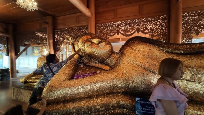 Οι άνθρωποι πιστεύουν ότι η τοποθέτηση του χρυσού στρώματος στο άγαλμα θα αυξήσει τον πλούτο της ζωής στο Sin Buri ThAiland στοκ εικόνα με δικαίωμα ελεύθερης χρήσης