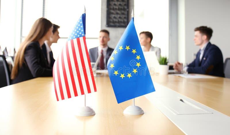 Οι άνθρωποι ποικιλομορφίας μιλούν τη συνεργασία Διεθνών Διασκέψεων Αμερικανική σημαία και σημαία της Ευρωπαϊκής Ένωσης στοκ φωτογραφία