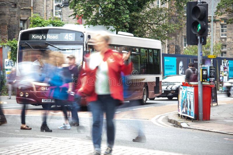 Οι άνθρωποι που διασχίζουν τη διάβαση πεζών στο Εδιμβούργο ως οδικό λεωφορείο βασιλιάδων περιμένουν στα φω'τα στοκ φωτογραφία