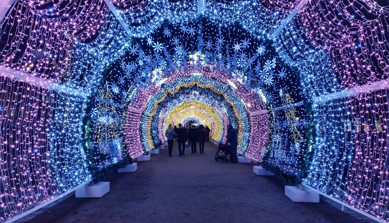 Οι άνθρωποι που περπατούν μέσω του όμορφου φωτεινού bluee και της ιώδους ελαφριάς σήραγγας στη Μόσχα σταθμεύουν κατά τη διάρκεια  στοκ εικόνες