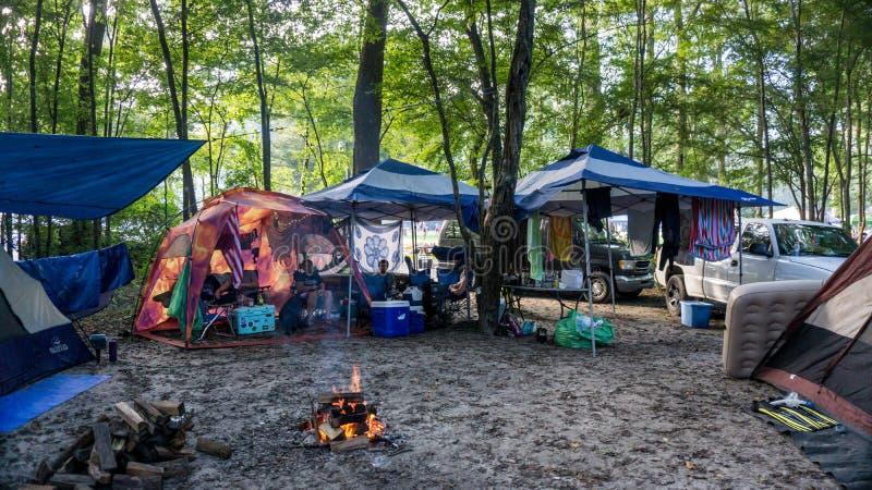 Οι άνθρωποι που χαλαρώνουν σε ένα ζωηρόχρωμο έδαφος στρατόπεδων γύρω από την πυρκαγιά με τις σκηνές, τα φορτηγά & τα οχήματα στο  στοκ εικόνες με δικαίωμα ελεύθερης χρήσης