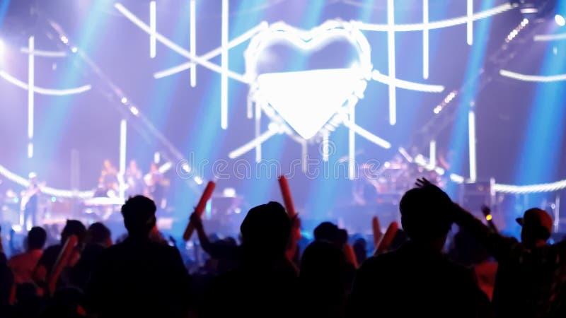 Οι άνθρωποι που χορεύουν με τη σκηνή ανάβουν στη συναυλία αιθουσών παρουσιάζουν στοκ φωτογραφία