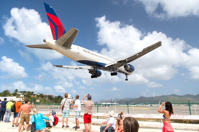 Οι άνθρωποι προσέχουν το έδαφος αεροπλάνων στον αερολιμένα σε Philipsburg, ST Maarten στοκ εικόνες
