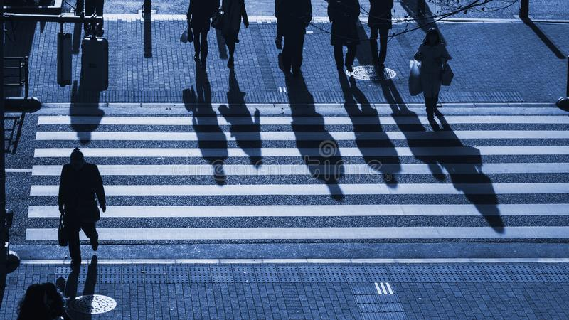Οι άνθρωποι σκιαγραφιών περπατούν στη για τους πεζούς διάβαση πεζών στη σύνδεση στοκ εικόνα