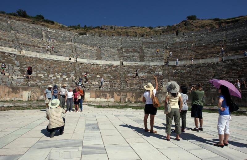 Οι άνθρωποι στέκονται στη βάση των ρωμαϊκών καταστροφών θεάτρων επί του αρχαίου τόπου Ephesus στην Τουρκία στοκ φωτογραφία