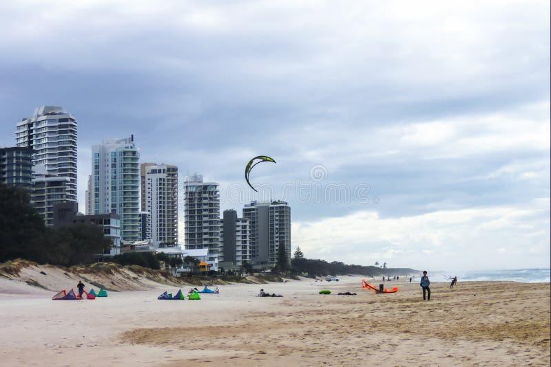 Οι άνθρωποι στην παραλία την ημέρα θύελλας που παίρνει έτοιμη στον ικτίνο κάνουν σερφ με έναν ικτίνο στον αέρα - το Gold Coast Qu στοκ εικόνα