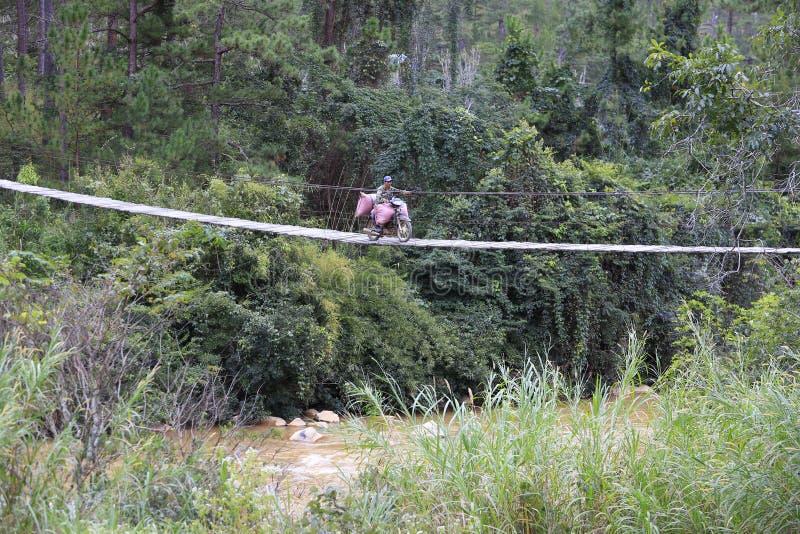 Οι άνθρωποι φέρνουν εκεί το προϊόν πέρα από την επικίνδυνη γέφυρα στοκ φωτογραφίες