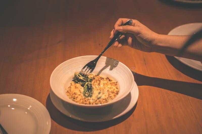 Οι άνθρωποι χρησιμοποιούν το δίκρανο για το τυρί σπανακιού επιλογών στο πιάτο στο εστιατόριο στοκ φωτογραφία με δικαίωμα ελεύθερης χρήσης