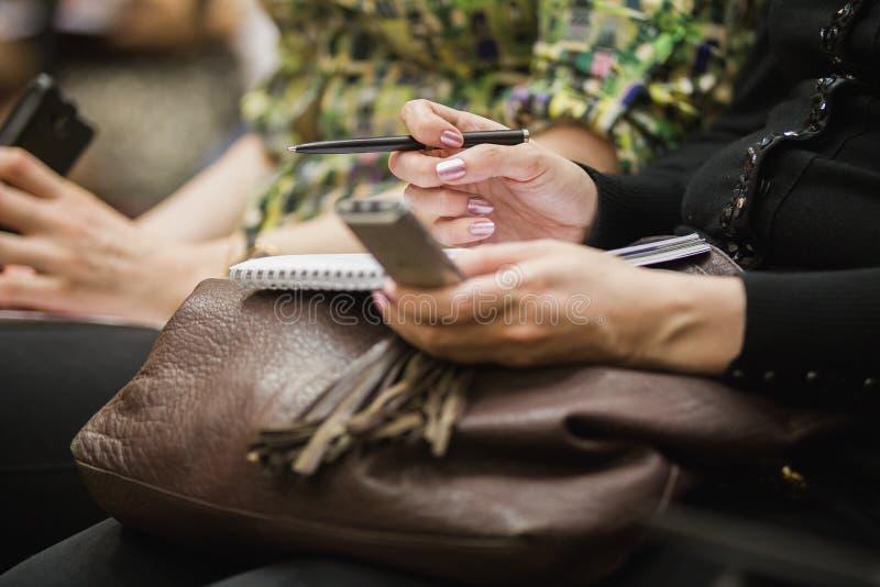 Οι άνθρωποι χρησιμοποιούν gadger κατά τη διάρκεια της εταιρικής Τύπος-διάσκεψης στοκ φωτογραφίες