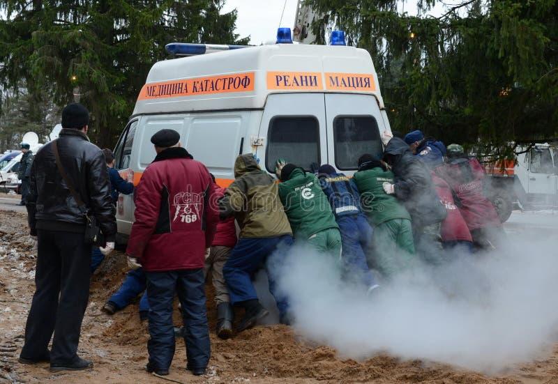 Οι άνθρωποι ωθούν ένα κολλημένο ασθενοφόρο νεκρανάστασης αυτοκινήτων στοκ φωτογραφίες με δικαίωμα ελεύθερης χρήσης