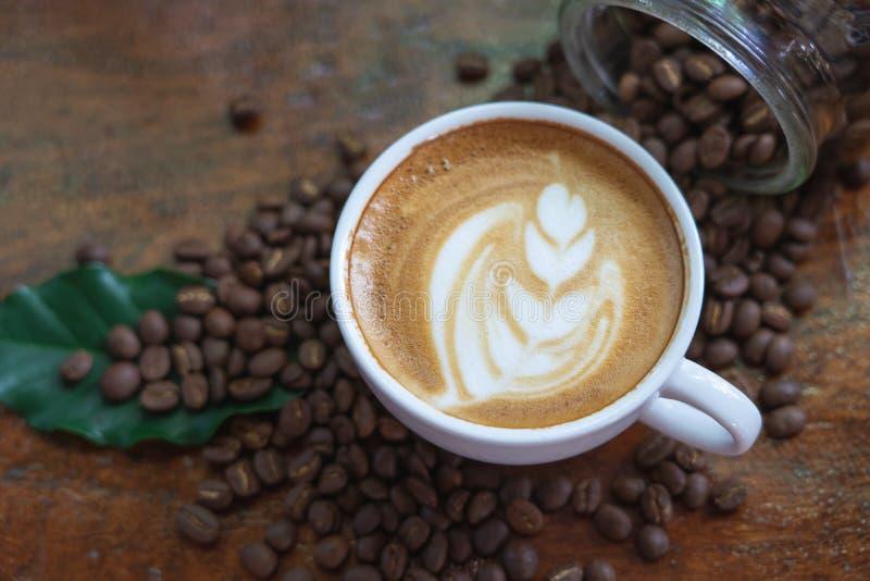 Οι άσπρα κούπες καφέ και τα φασόλια καφέ έχυσαν σε έναν ξύλινο πίνακα, που τακτοποιήθηκε υπέροχα, που διακοσμήθηκε με τα φύλλα κα στοκ εικόνες