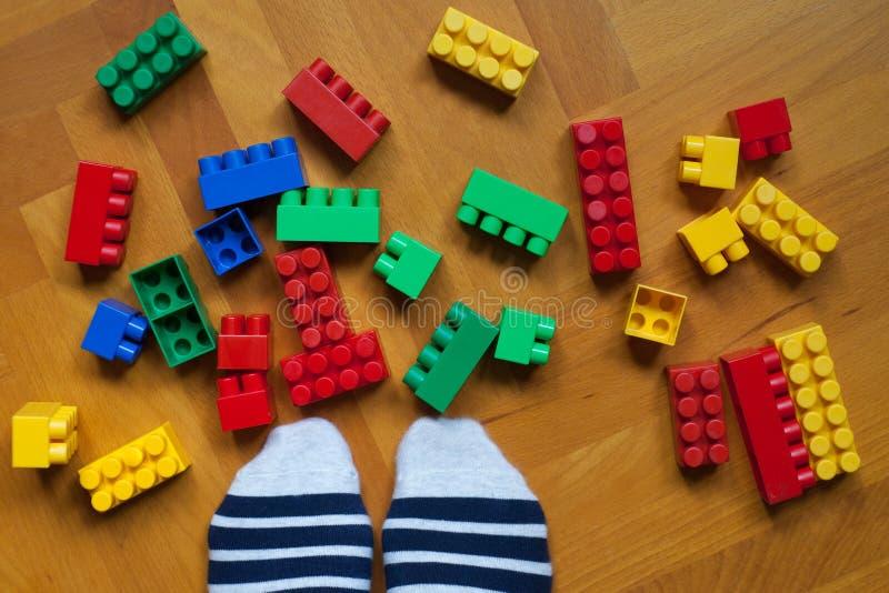 Οι άσπρες μπλε κίτρινες κόκκινες κατασκευές κύβων λωρίδων καλτσών ποδιών μπερδεύουν το πάτωμα παιχνιδιών παιχνιδιών ξύλινο στοκ φωτογραφίες