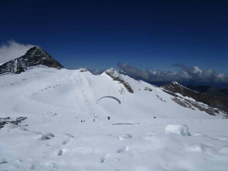 Οι Άλπεις - δύσκολα βουνά με το χιόνι το καλοκαίρι, Αυστρία, μπλε ουρανός με το ανεμόπτερο στοκ εικόνα με δικαίωμα ελεύθερης χρήσης