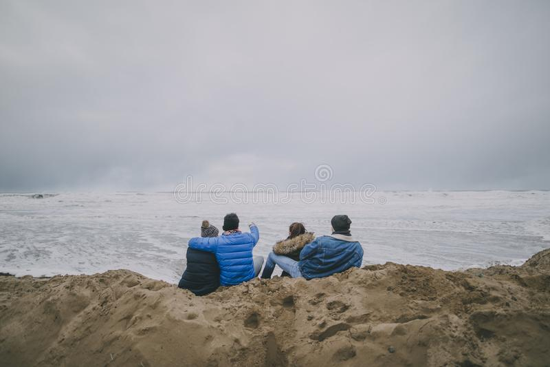 Οι έφηβοι κάθονται σε μια χειμερινή παραλία στοκ εικόνα