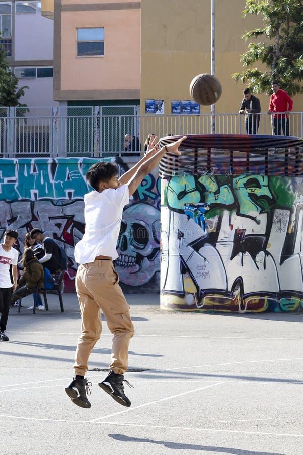 Οι έφηβοι παίζουν την καλαθοσφαίριση οδών ή streetball Αθλητισμός, υγιείς τρόπος ζωής και παιχνίδια ομάδων στην οδό της Βαρκελώνη στοκ φωτογραφία