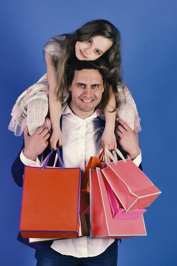 Οι αγορές, παρουσιάζουν και οικογενειακή έννοια Κορίτσι και άτομο με τις ευτυχείς τσάντες αγορών λαβής προσώπων στοκ εικόνα