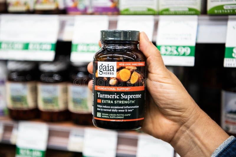 Οι αγοραστές δίνουν το κράτημα ενός πλαστικού μπουκαλιού των vegan υγρών φυτο καλυμμάτων της Gaia Herbs Brand Turmeric στοκ εικόνα
