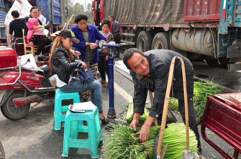 Pengzhou, Κίνα: Αγρότες που ζυγίζουν τα πράσινα σκόρδου στοκ εικόνες